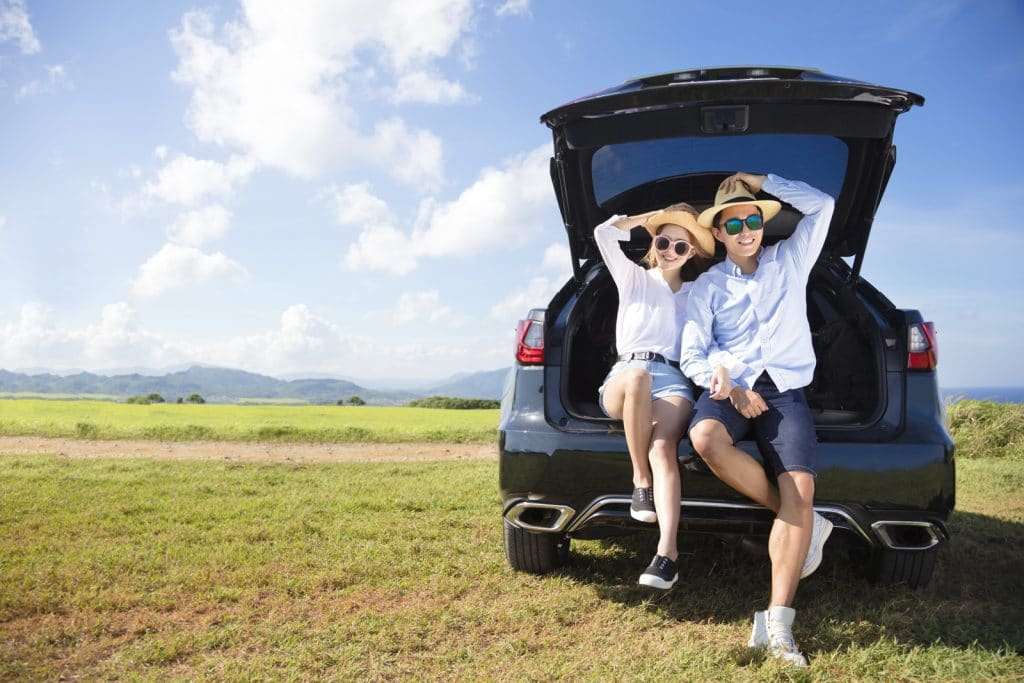 a couple relaxing on their car boot in a rural area