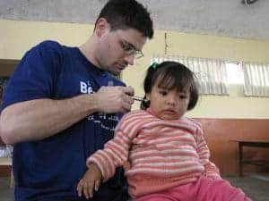Dr Jeff treating a child's neck in Peru