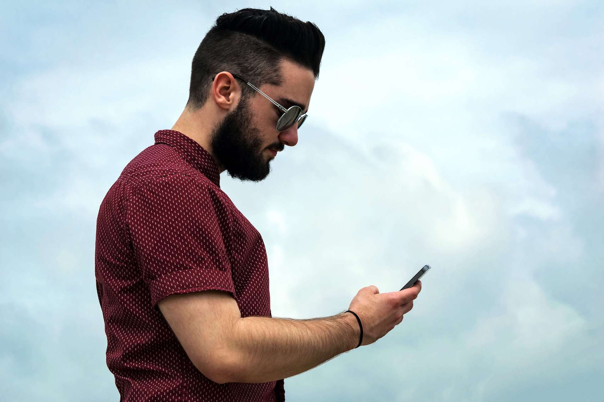 Man holding a Phone and lowering his neck