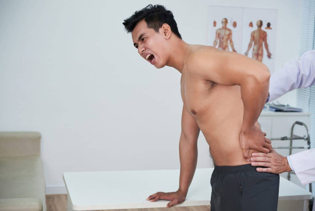 SG Pain Solution Young man suffering severe pain from slipped disc in his lower back
