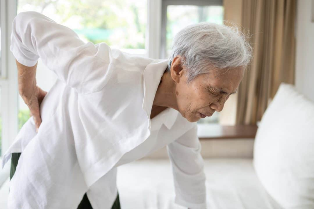 Sad asian senior woman with back and hip joint painful while standing