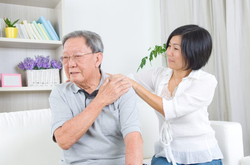 Asian old man shoulder pain, sitting on sofa , daughter massaging father shoulder. Chinese family, senior retiree indoors living lifestyle at home.